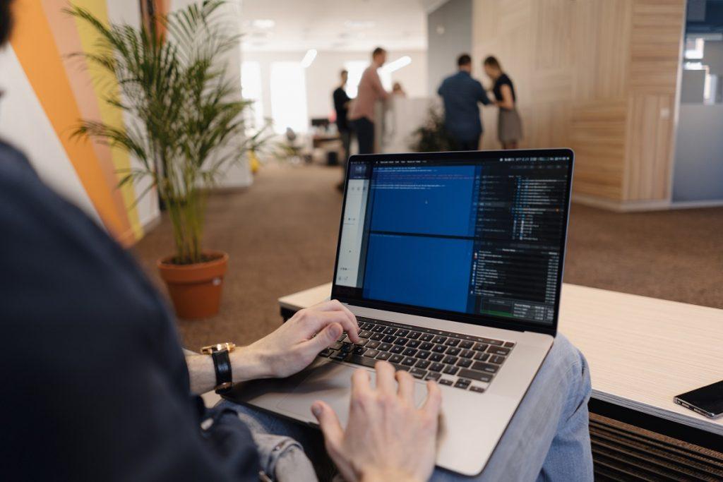 close up man writing code laptop